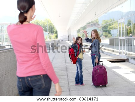 School girls waving goodbye at their mother - stock photo
