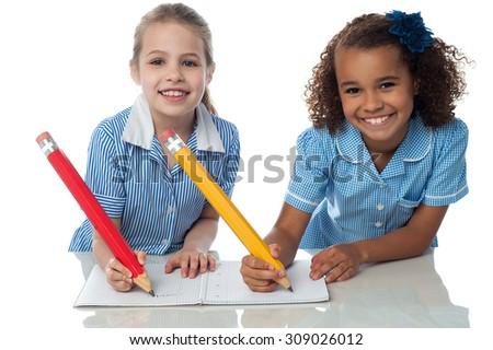 School girls writing homework together - stock photo