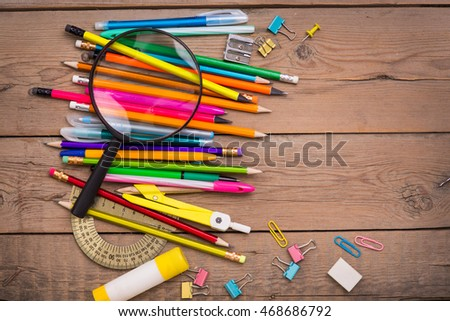 School items on a wooden table, Pencils and student pens on a wooden surface
