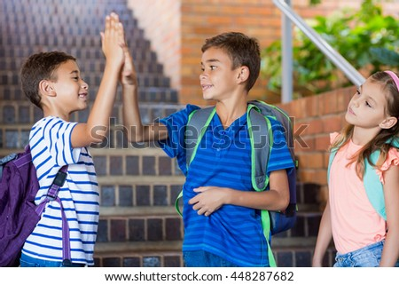 School kids giving high five on staircase at school - stock photo