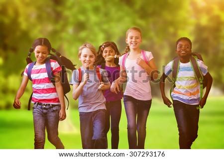 School kids running in school corridor against trees and meadow - stock photo