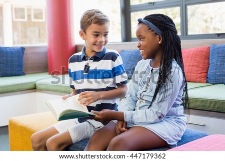 School kids sitting together on sofa and reading a book in library - stock photo