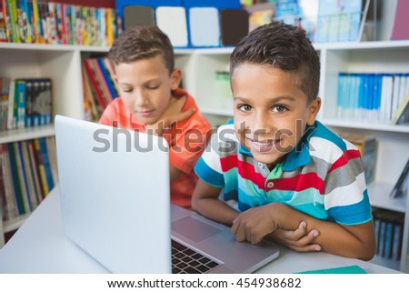 School kids using a laptop in library at school