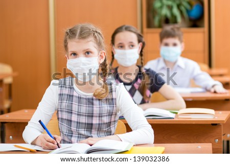 school kids with protection mask against flu virus at lesson in classroom - stock photo
