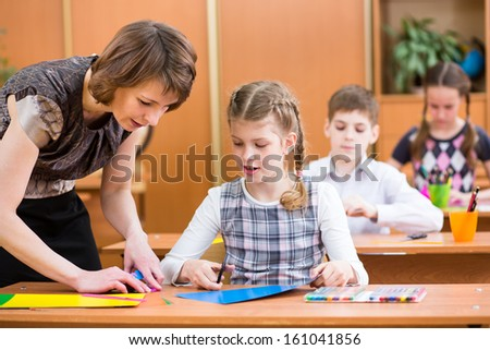 School kids work at labour lesson. Teacher helping pupil.