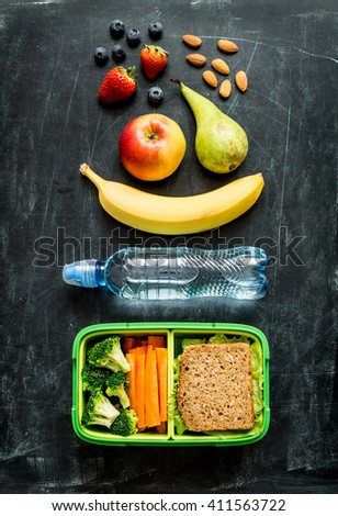 School lunch box with sandwich, vegetables, water, almonds and fruits on black chalkboard background. Healthy eating habits concept. Flat lay composition (from above, top view). - stock photo
