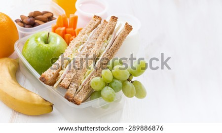 school lunch with sandwiches and fruit on white background, close-up - stock photo