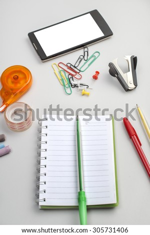 School materials such as crayons, notebooks, clips, stapler, prencils on table - stock photo