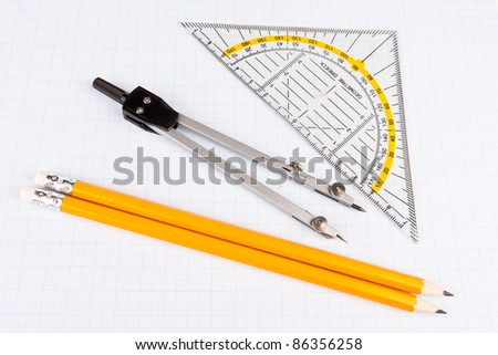 School mathematics tools on squared paper - stock photo