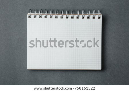 school notebook on a dark gray background, spiral notepad on a desk
