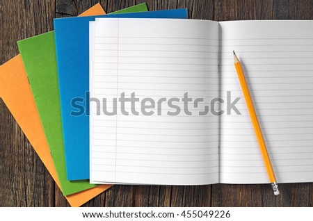 School notebooks and pencil on dark wooden table, top view - stock photo