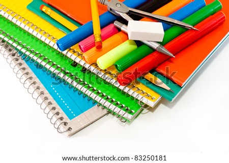 school notebooks, pens, compasses and a pencil on a white background