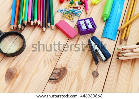 school objects isolated on a wooden background - stock photo