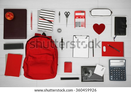 School set with backpack, heart and supplies on light wooden background - stock photo