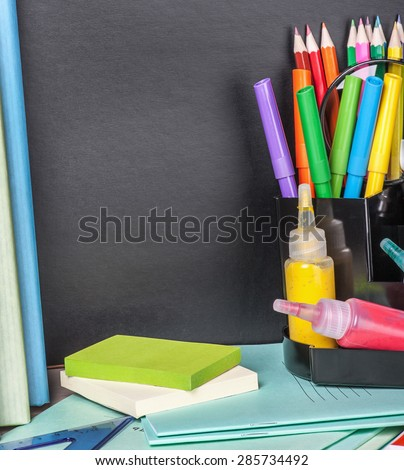 school stationery laid on a background of chalkboard. Space for text. Focus on chalkboard - stock photo