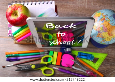 school stuffs and written text on tablet pc on wooden background-top view - stock photo