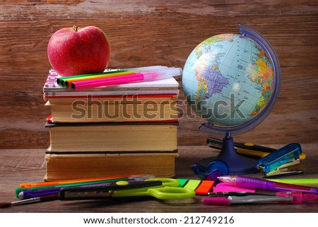 school stuffs with globe and apple on wooden background  - stock photo
