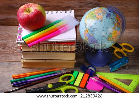 school stuffs with globe and apple on wooden background-top view