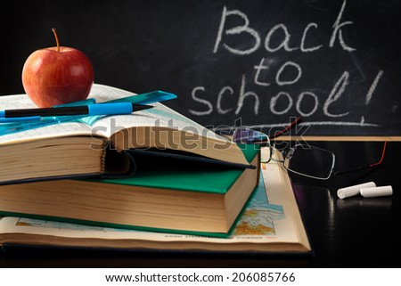 School supplies against blackboard. - stock photo