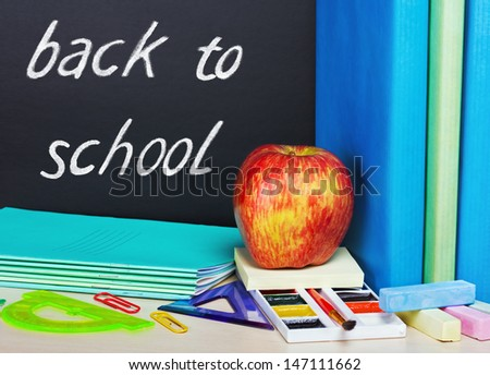 school supplies and a blackboard with text back to school - stock photo