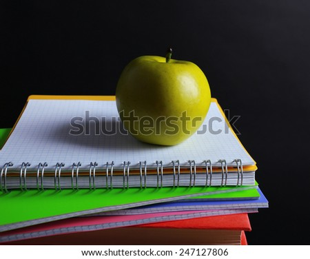 School supplies and apple on black background - stock photo