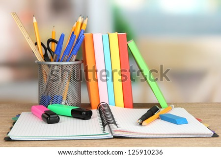 School supplies and books on wooden table - stock photo