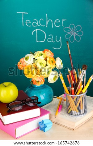 School supplies and flowers on blackboard background with inscription Teacher Day - stock photo