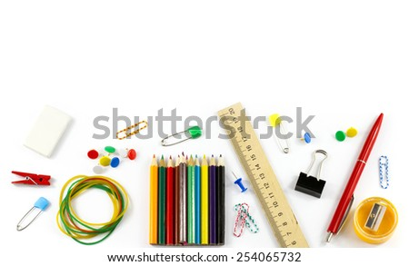School supplies: colored pencils, wooden yardstick, erasers, binders, stationery gum, paper clips, pencil sharpener, a small clothespin, colored pins and pen isolated on white background - stock photo