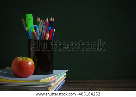 School supplies on a wooden surface against a blackboard. Books, notebooks, handles, colored pencils and rulers in a glass, red apple on a wooden table
