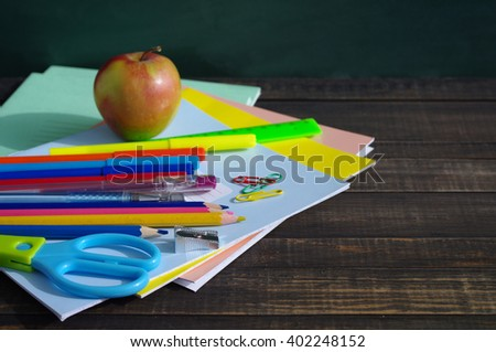 School supplies on a wooden table against a blackboard. Notebooks, handles, pencils, scissors and apple against a green blackboard - stock photo