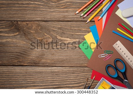 School supplies on a wooden table with space for text, top view - stock photo
