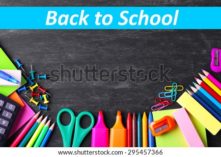 School supplies on blackboard background - stock photo