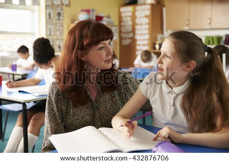 School teacher helping a girl at her desk in class, close up - stock photo
