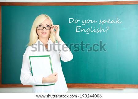 School teacher near blackboard in classroom - stock photo