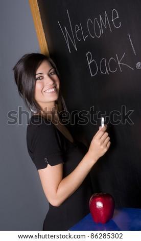 School Teacher Writes Welcome to Class on Blackboard Chalk Board - stock photo