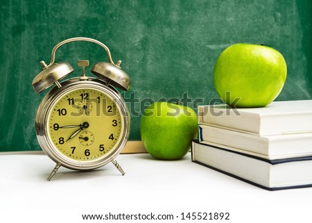 School time again. Clock, apples and books on teacher's table, green chalkboard in background. Back to school. - stock photo