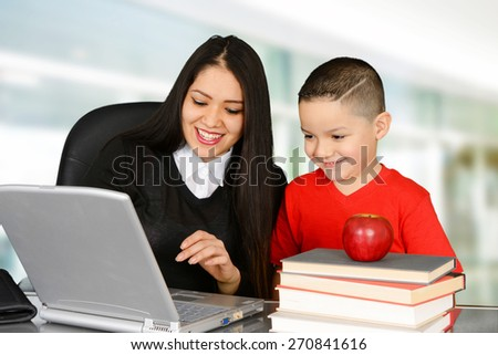 Schoolboy and teacher looking at laptop in class - stock photo