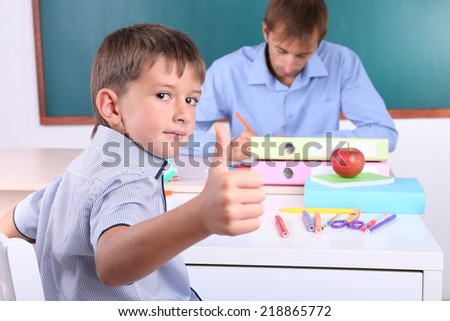 Schoolboy and teacher sitting in classroom on blackboard background - stock photo