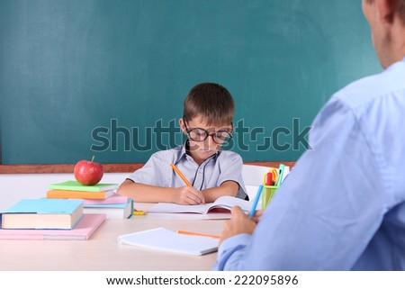 Schoolboy and teacher sitting in classroom on blackboard background - stock photo