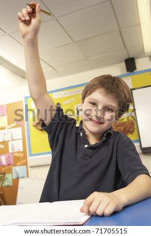 Schoolboy Answering Question In Classroom - stock photo