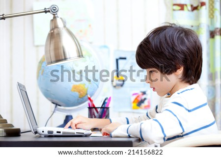 schoolboy at a desk working on a computer - stock photo