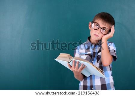 Schoolboy at blackboard in classroom - stock photo