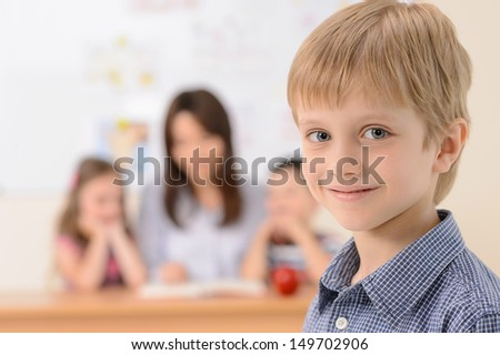 Schoolboy. Cheerful schoolboy smiling at camera while teacher with pupils sitting on the background - stock photo