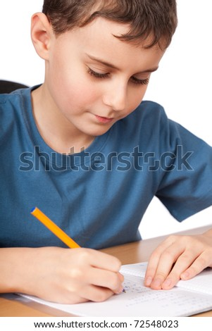 Schoolboy doing his homework at his desk - stock photo