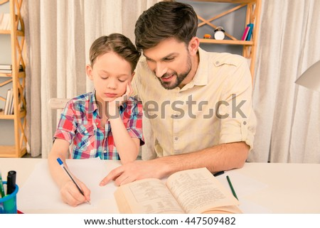 Schoolboy doing hometask with father and writting in workbook - stock photo