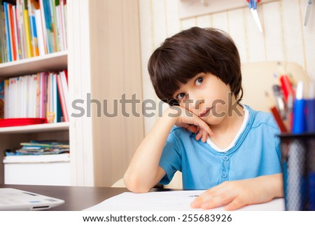 schoolboy doing homework and fooling around - stock photo