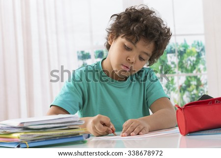 schoolboy doing homework at his desk - stock photo