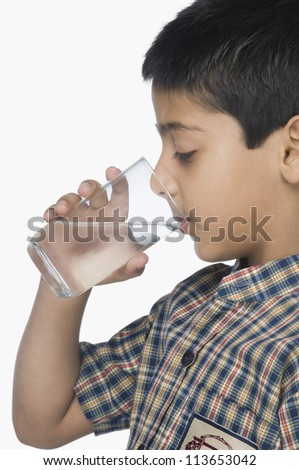 Schoolboy drinking a glass of water - stock photo