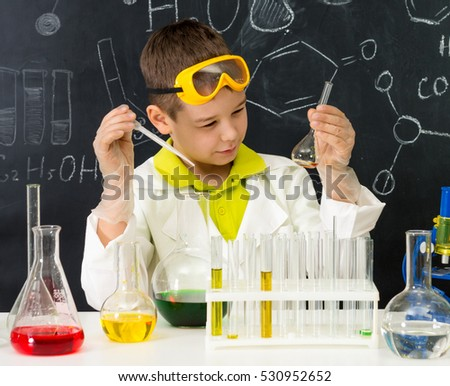 schoolboy  gown and gloves watching chemical experiment in tube in chemistry lab