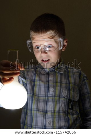 schoolboy holding glowing bulb - stock photo